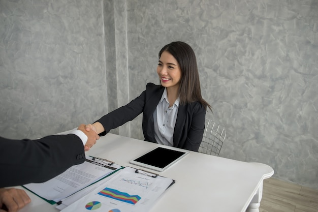 Les gens d'affaires se serrant la main tout en restant assis sur le lieu de travail