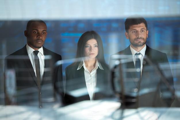 Les gens d'affaires se tiennent au-dessus de l'écran virtuel
