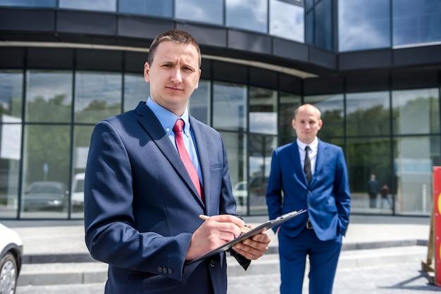 Les gens d'affaires signant un contrat près de gratte-ciel à l'extérieur