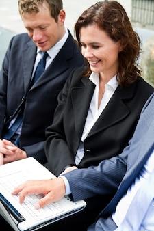 Gens d'affaires avec tablette signature de contrat sur un banc