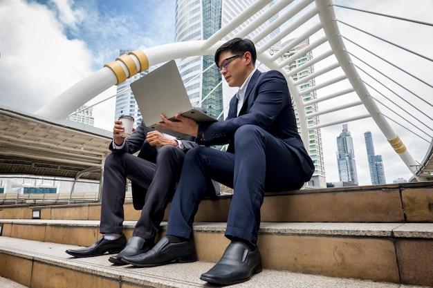 Gens d'affaires tenant un ordinateur portable et discutant en étant assis sur la passerelle