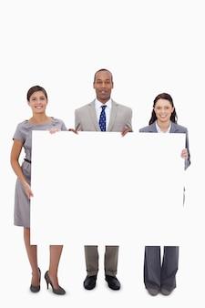 Les gens d'affaires tenant une pancarte blanche