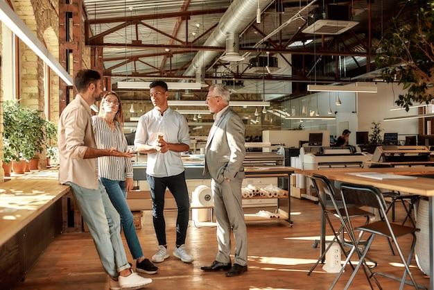 Gens d'affaires tenant des tasses à café et parlant de quelque chose tout en se tenant dans le bureau moderne