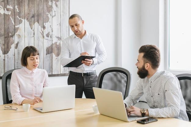 Gens d'affaires travaillant avec un ordinateur portable au bureau