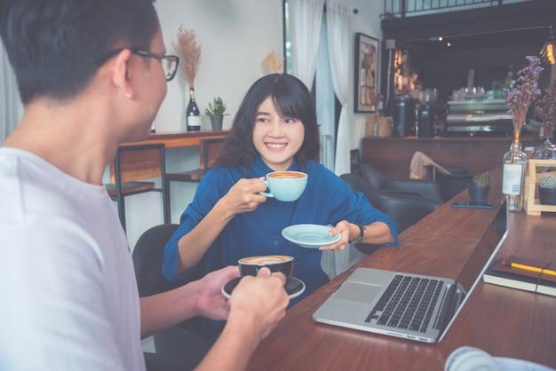 Gens d'affaires travaillant avec ordinateur portable et boire du café dans un café