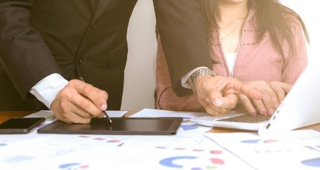 Les gens d'affaires travaillent avec l'analyse graphique en utilisant des ordinateurs et des smartphones