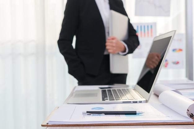 Les gens d'affaires utilisant un ordinateur portable et des graphiques financiers à la réunion o