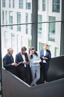 Gens d'affaires utilisant un téléphone mobile et une tablette numérique