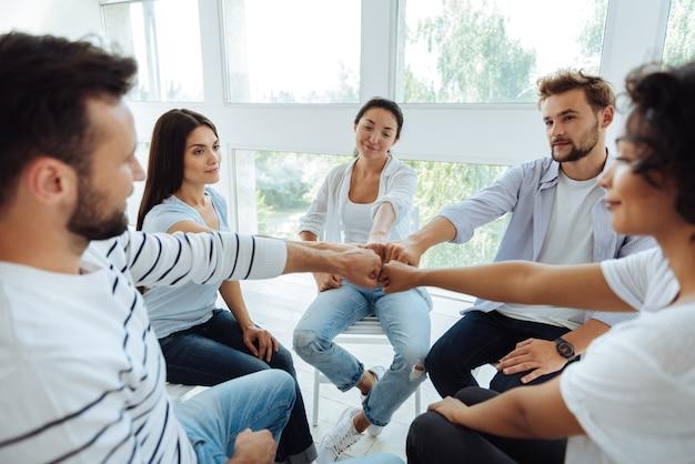 Des gens agréables et joyeux assis dans le cercle et souriant tout en démontrant leur unité