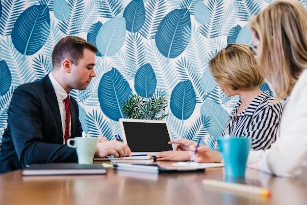 Les gens assis et coworking à l'ordinateur portable