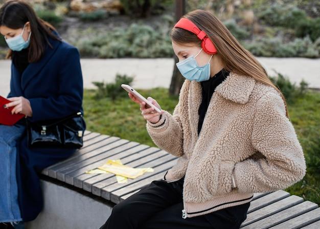 Des gens assis à distance et portant un masque
