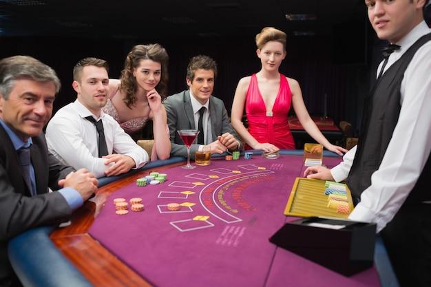 Les gens assis à la table de blackjack, souriant au casino