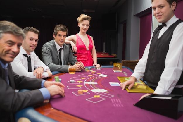 Les gens assis à la table de blackjack et souriant