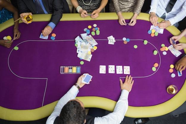 Les gens assis à table en jouant au poker