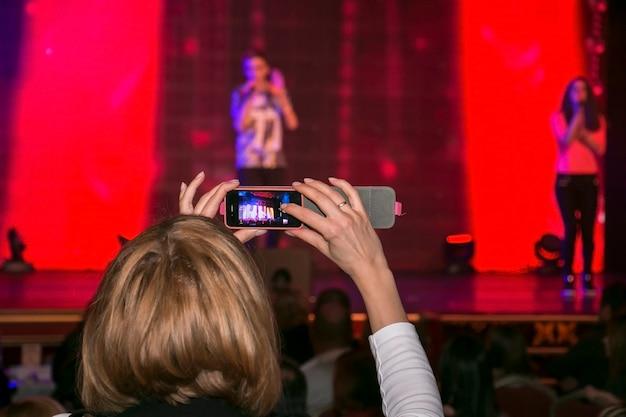 Les gens au concert filment une vidéo ou une photo.