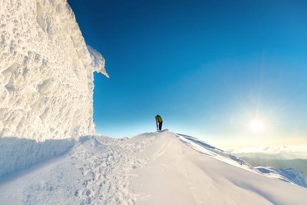 Les gens au sommet de la montagne d'hiver dans la neige au coucher du soleil