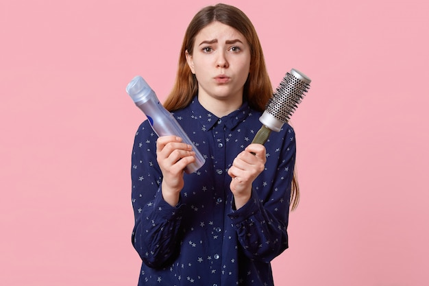 Gens, beauté, concept de toilettage. une jeune femme mécontente fait la moue, vêtue d'une chemise élégante, pose sur un mur rose avec de la laque et un peigne, vient chez le coiffeur pour la coiffure.