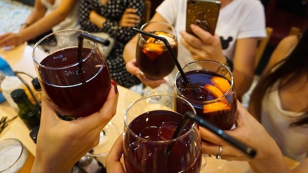 Les gens boivent un cocktail. de l'alcool. club. une joyeuse compagnie au bar tient des verres de sangria rouge. concept de vacances en espagne