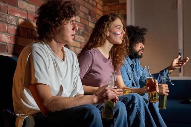 Des gens bouleversés qui regardent un match de sport, un championnat à la maison, s'inquiètent de jouer au basket-ball national préféré, au tennis, s'asseoir sur un canapé et boire de la bière, manger du pop-corn