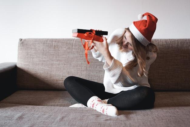 Les gens célébrant l'amour et le bonheur de noël concept beauté fille ouverture cadeaux présents assis sur un canapé à la maison