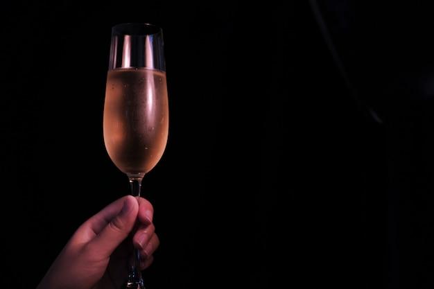 Gens de célébration de noël ou du nouvel an les mains avec des verres de cristal plein de champagne près de l'arbre de noël et de l'espace pour votre texte.