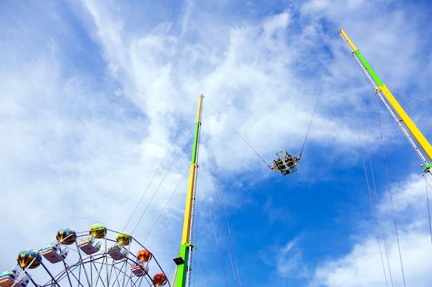 Les gens à cheval en l'air sur un carrousel dangereux sur fond de ciel bleu, concept de vacances d'été