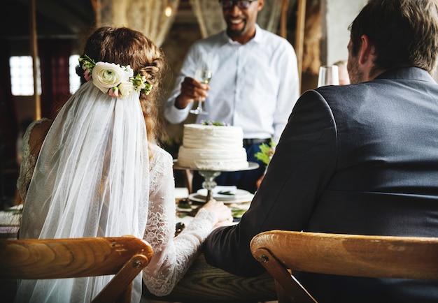 Les gens collent des verres de vin sur la réception de mariage avec les jeunes mariés