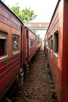 Les gens communiquent depuis les fenêtres de divers trains arrêtés à la gare