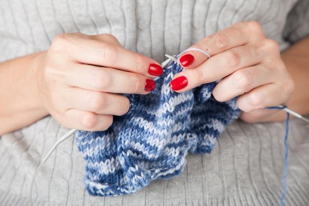 Les gens et le concept de couture - une femme tricote avec du fil de laine à tricoter