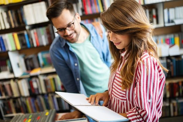 Les gens, les connaissances, l'éducation étudient le concept d'école. groupe d'étudiants heureux lisant des livres et se préparant à l'examen en bibliothèque