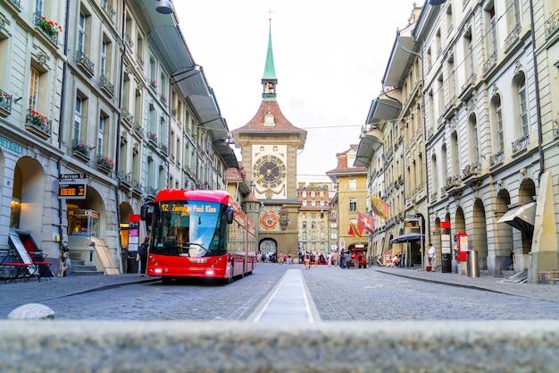 Gens dans une allée commerçante avec la tour de l'horloge astronomique zytglogge de berne en suisse