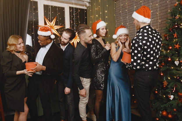 Les gens dans une décoration christman. homme en costume noir. célébrations de groupe nouvel an.