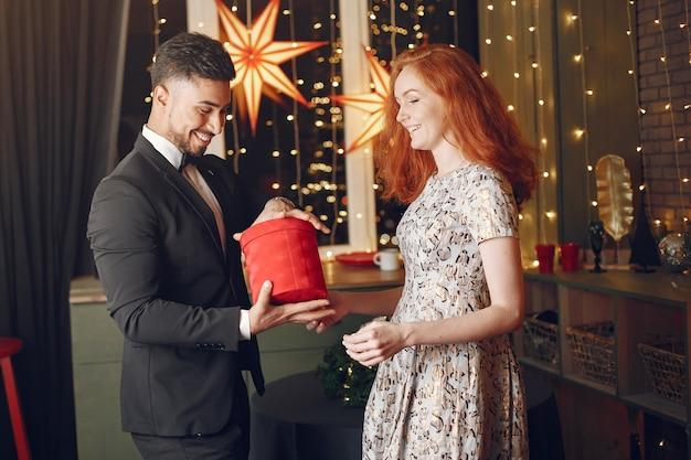 Les gens dans une décoration christman. homme en costume noir. femme avec boîte rouge.