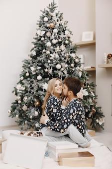 Les gens dans une décoration christman. homme et femme dans un pyjama identique. famille à la maison.