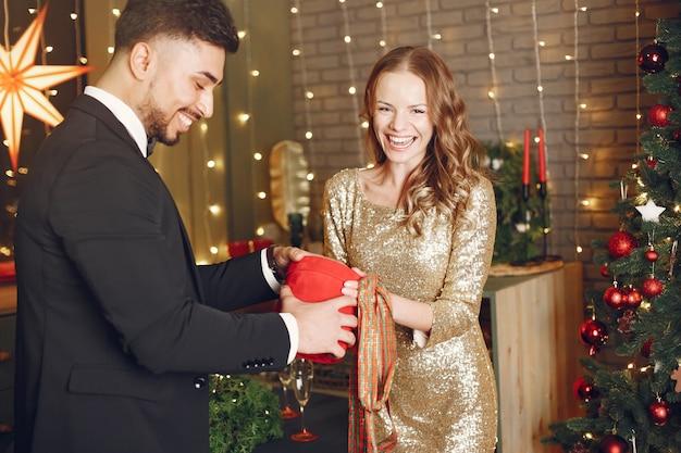 Les gens dans une décoration de noël. homme en costume noir. femme avec boîte rouge.