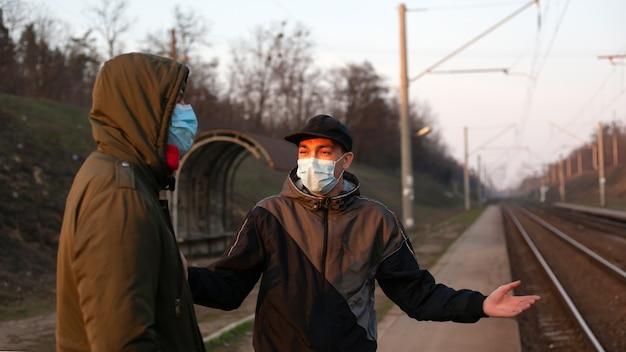 Les gens dans des masques médicaux à la gare attendent le train. arrêt des transports en commun, mise en quarantaine en raison d'une épidémie de coronavirus
