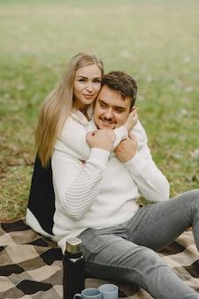 Les gens dans un parc. femme en manteau marron. homme dans un pull blanc. couple dans un pique-nique.
