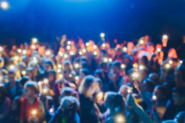 Les gens debout, les bras levés, tournent une vidéo sur le téléphone à un spectacle de musique de rue, arrière-plan flou.
