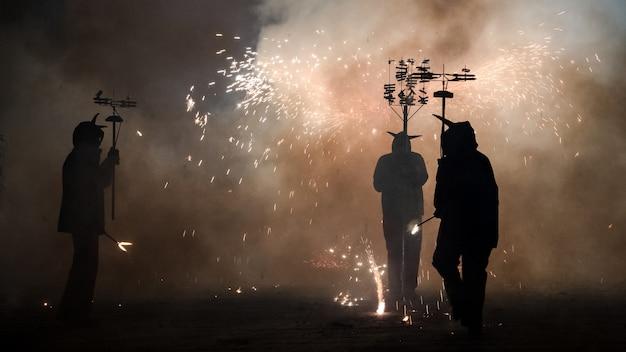 Des gens déguisés en démons faisant un spectacle pyrotechnique