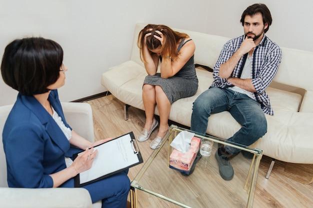 Des gens désespérés sont assis dans la chambre avec un thérapeute et travaillent avec elle. fille regarde vers le bas et tient ses mains dans les cheveux. guy regarde le psychologue et réfléchit. le docteur les regarde.