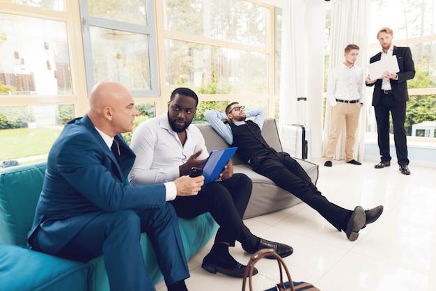Les gens discutent dans une pièce avec des fenêtres panoramiques.