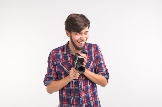 Gens drôles, photo et concept vintage - jeune homme à l'aide d'un appareil photo vintage sur fond blanc