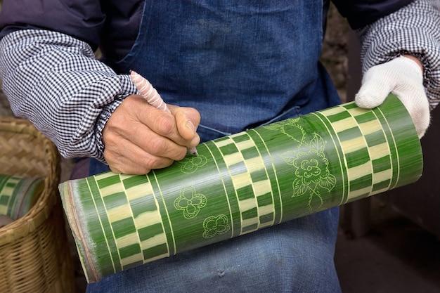 Les gens écrivent des motifs en bambou.