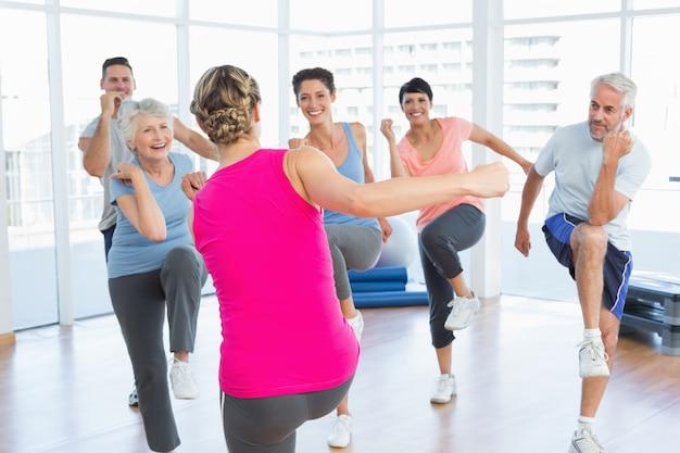 Gens, faire des exercices de remise en forme de puissance au cours de yoga dans un studio de fitness