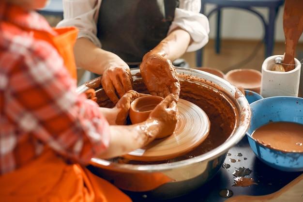 Les gens faisant une vaze d'une argile sur une machine de poterie