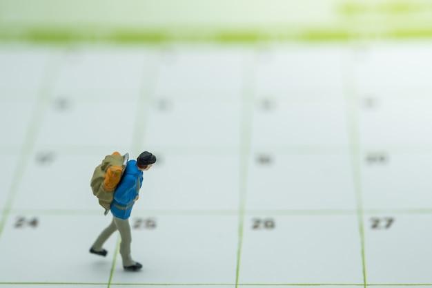 Gens de figurine miniature voyageur avec sac à dos marchant sur le calendrier