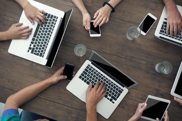 Gens avec des gadgets à table en bois, vue de dessus