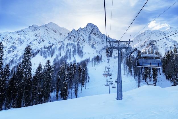 Les gens grimpent au sommet de la montagne sur le télésiège de la station de ski rosa khotor en fédération de russie