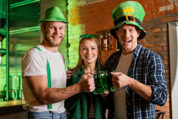 Des gens heureux célébrant st. la journée de patrick au bar