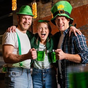 Des gens heureux célébrant st. patrick's day au bar avec boissons